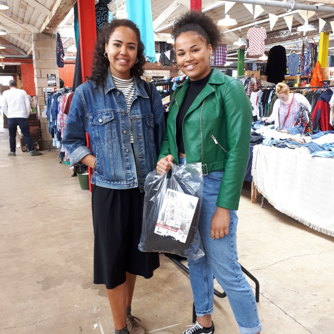 Two happy customers with a bag of vintage clothes leaving the Fab Fill A Bag vintage fashion sale
